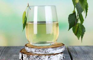 березовый сок в стакане на пеньке