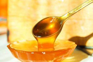 натуральный мед, стекающий с чайной ложки