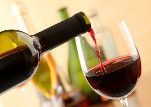 процесс наполнения бокала красным вином