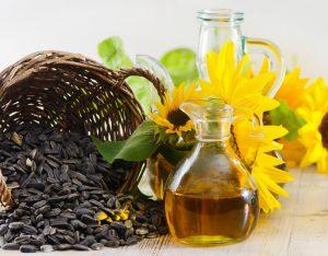 подсолнечное масло и семена подсолнуха на фоне его цветка