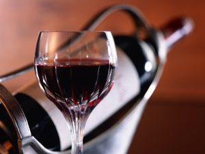 бокал красного вина на фоне бутылки